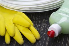 Detergent, dishes and latex gloves Stock Photos