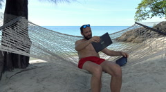 Young man using modern laptop while sitting on hammock on beach  Stock Footage