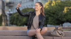 Selfie Cute fashion woman using iPhone smart phone camera sitting on steps - stock footage