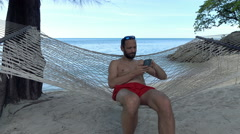 Young man listening to music on cellphone and singing lying on hammock on beach Stock Footage