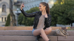 Cute hipster girl taking selfie with smart phone using iPhone camera in city - stock footage