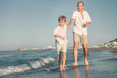 Father with son running together on the sea surf line - stock photo