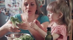 Smiling woman and girl preparing salad - stock footage