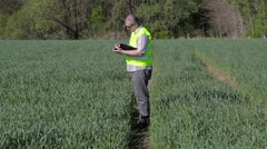Farmer writing and walking on the green cereal field Stock Footage