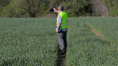 Farmer take pictures on smartphone and walking on the green cereal field Stock Footage