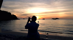 Male hand taking picture of sunset with cellphone on beach Stock Footage