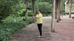 An elderly Chinese woman shows the tricks in the street Stock Footage