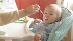 Mother Spoon Feeding A Boy Stock Footage