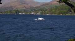 Small boat taking in a tour of Lake Windermere, Claife, Cumbria, UK - stock footage