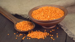 Red lentils in a ceramic bowl on old wooden table ( dolly shot ) Stock Footage
