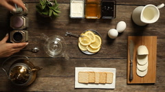 Lemon tea and fruit candy on wooden table. Stock Footage