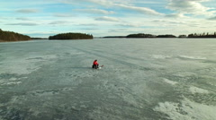 Aerial orbit shot of a fisherman ice fishing at a frozen lake in springtime Stock Footage