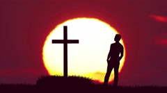 The man stand near the cross against the background of sunrise. Real time  Stock Footage