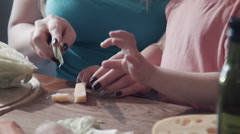 Close-up of daughter cutting cheese on wooden board with mother Stock Footage