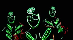 4 people dancing in costumes of LEDs Stock Footage