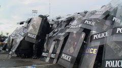 Wall of Riot Police in Full Combat Gear Confront Protesters Shields 9678  - stock footage