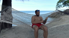 Young man reading book while sitting on hammock on beach Stock Footage