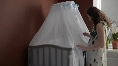 Beautiful Young mother stands near the cot of her newborn child - stock footage