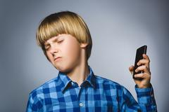 Closeup Portrait of worried stressed boy with mobile going irritation on gray Stock Photos
