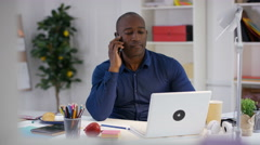4K Businessman working at desk in office, working on laptop & talking on phone Stock Footage