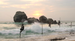 Stilt fishermen fishing, sunset, nr Galle, SW Coast, Sri Lanka - stock footage
