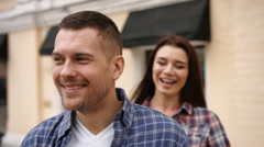 Young woman in checkered shirt embracing her smiling boyfriend from behind Stock Footage