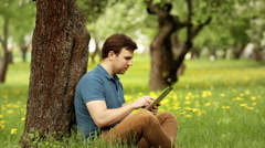 Pretty smiling hipster man using his tablet pc on a sunny day Stock Footage