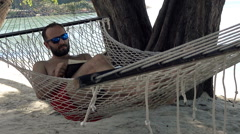 Young man reading book while lying on hammock on beach Stock Footage
