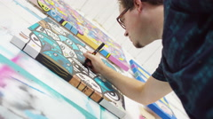 4K Modern graphic artist working on a canvas in his studio - stock footage