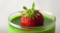Rotating green pannacotta dessert with strawberry 4K macro video Stock Footage