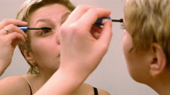 Pretty woman applying eyelashes mascara makeup Stock Footage
