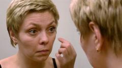 Pretty woman applying eyelashes mascara makeup - stock footage