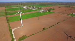 Giant wind turbines tower over rural farms and fields Stock Footage