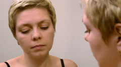 Woman applies makeup concealer foundation cream Stock Footage