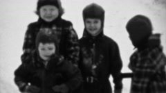 1937: Pack of rascal kids bundled for cold weather winter snow. Stock Footage