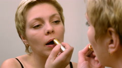 Pretty blond woman applying red lipstick makeup Stock Footage