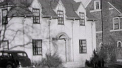 1937: Wealthy suburban white brick house car parked in driveway. Stock Footage