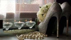 High heel stiletto shoes, bouquet of white roses, jewelry and lit candles on  Stock Footage