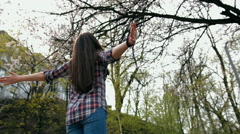 Happy smiling brunette woman in checkered shirt turning with arms outstretched - stock footage