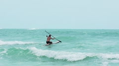 Man on sup borad riding the waves in a sea storm. Slow motion Stock Footage
