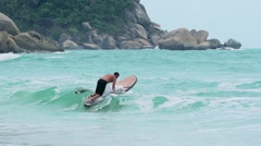 KOH PHANGAN, 2015: Man on sup board start riding the waves in a sea storm Stock Footage