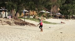 KOH LIPE, CIRCA 2015: Asian man carries a load on his back on the beach Stock Footage