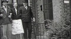 1937: Lady escorted by gentleman doorstep to sidewalk streets. Stock Footage