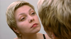 Woman plucks and pulls her eyebrows out at mirror Stock Footage