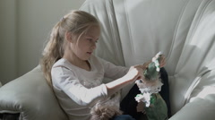 Adorable little girl playing in her room with doll - stock footage