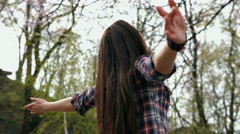 Happy smiling brunette woman in checkered shirt and blue jeans turning and Stock Footage