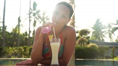 Beautiful attractive girl drinking cocktail Pina ?olada in the swimming pool Stock Footage