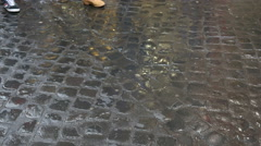 People legs jeans walking the wet paved street stone blocks after rain in Rome Stock Footage