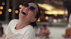 Portrait of a beautiful young girl in sunglasses fooling around on the beach Stock Footage