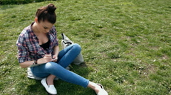 Young woman in casual clothes writing in her journal sitting on grass in the - stock footage